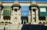 "View of main entrance with people showing, left to right, banners for the exhibitions ""The..."
